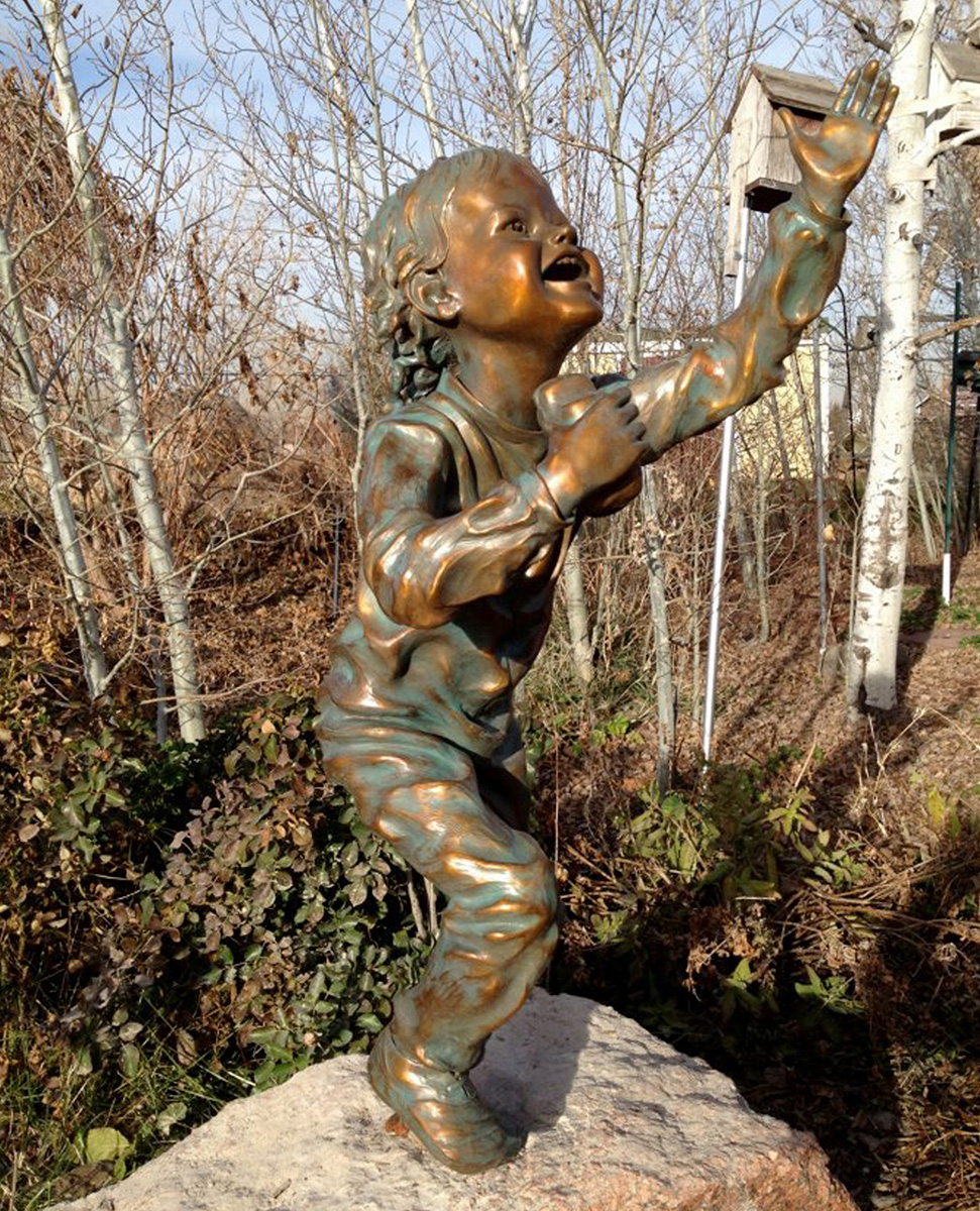 Bronze sculpture of a young boy, full body