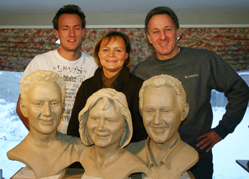 Family poses with clay sculpture